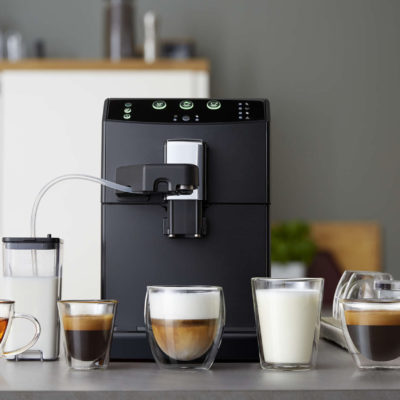 Automatic coffee machine and drinks in glass cups in the kitchen