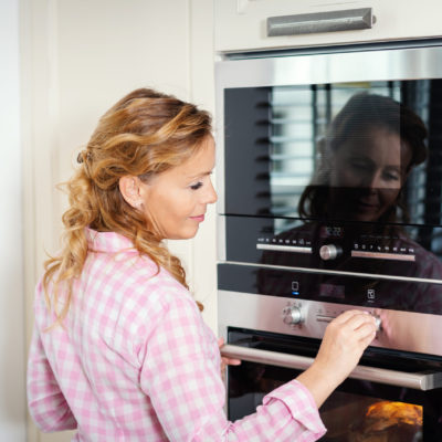 smiling woman turning on the oven in the kitchen
